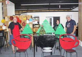 CAIRO COFFEE COMPANY is already getting in the Christmas spirit, and owners Janet and David Wynne invite community children to come help them create ornaments to complete their holiday window the weekend after Thanksgiving. Looking on as the Wynnes place their wooden trees is Al Rocuant, right.