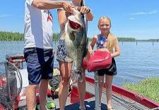 CLAY AND AMANDA PARKER of Valdosta hold up this 14.6 lb. bass caught Saturday at Tired Creek Lake. The mammoth fish is currently the Tired Creek Lake record fish. The family was not participating in the Cairo Rotary Club Fishing Tournament Saturday, but were fishing at the same time the event was taking place. According to Rotarian Chip Wells, seeing that record fish was icing on the cake to a great day on Tired Creek Lake.